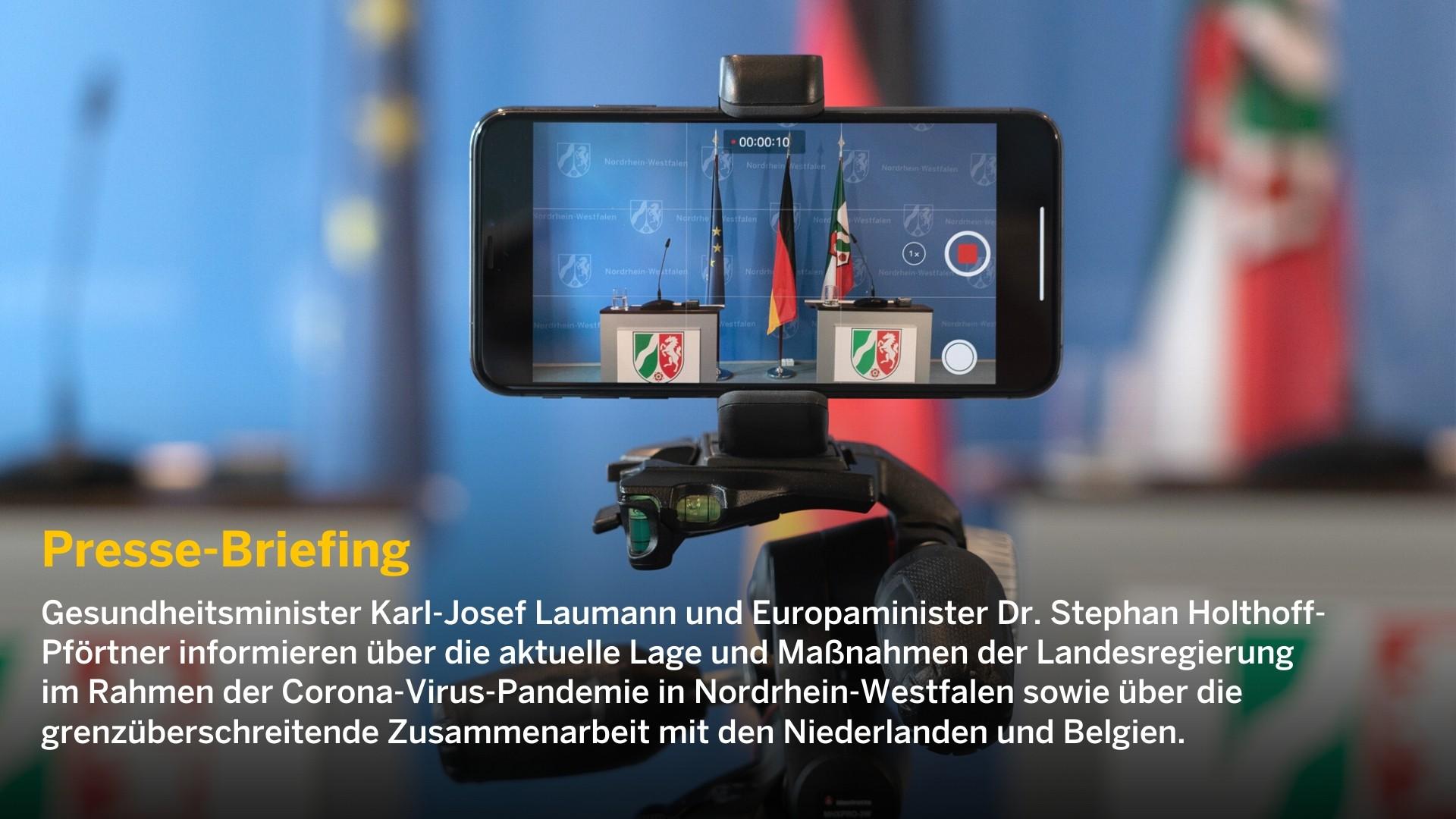 Ein Smartphone filmt 2 Rednerpulte auf einer Pressekonferenz