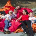 Mehrere Kinder ruhen sich mit ihrer Trainerin nach dem Sport auf großen, roten und orangefarbenen Kissen aus.