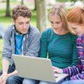 Schüler bzw. Jugendliche auf Parkbank vor Laptop