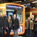 Ein Gruppe Menschen ssteht vor einer U-Bahn, die mit der Werbung der Finanzverwaltung NRW verziert ist