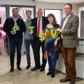 Staatssektretärin Milz hält mit drei Mitgliedern des Post-Telekom-Sportverein 1925 Aachen e.V. die vier Buchstaben P, T, S und V in grün jeweils in den Händen in Richtung Kamera..
