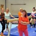 Staatssekretärin Milz in orangefarbenem T-Shirt und Sporthose mit sechs Damen in einer Turnhalle. Zwischen den Damen stehen zwei Schwebebalken, auf dem Boden liegen blaue Bodenmatten.