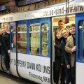 Ein Gruppe Menschen schaut aus einer U-Bahn, die mit der Werbung der Finanzverwaltung NRW verziert ist