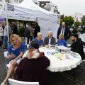 Ehrenamtstour-Veranstaltung: Eine Gruppe sitzt an einem runden Tisch, rechts steht der Ehrenamtstourbus, hinten steht ein Pavillonzelt.