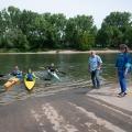 Staatssekretärin Milz steht am Ufer eines Sees. Auf dem See sind drei Kanufahrer. Am gegenüberliegenden Ufer stehen Bäume.