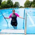 Eine Schwimmerin im pink-schwarzen Neoprenanzug, mit schwarzer Badekappe und schwarzer Schwimmbrille steigt aus einem offenen Schwimmbecken, ihre beiden Hände jeweils links und rechts am Geländer.