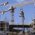 Auf dem Bild zu erkennen sind mehrere Baukräne auf einer Baustelle.