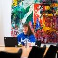 Staatssekretärin Milz sitzt an einem beigen Besprechungstisch mit schwarzen Stühlen. Vor sich ein schwarzes Notebook, links von ihr die Flaggen von Detuschland und NRW. Hinter sich an der Wand befindet sich ein großes, farbiges Kunstwerk mit einem großen NRW-Wappen oben mittig, verschiedene farbige Motive wie der Kölner Dom, die Hohenzollernbrücke gehen farblich abwechselnd ineinander über.