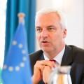 Minister Duin vor einer NRW und einer EU-Tischflagge