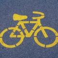 auf Asphalt ist eine gelbe Markierung in Form eines Fahrrades