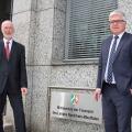 Zwei grauhaarige Männer in Anzügen stehen vor dem Schild des Finanzministeriums