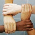 Nahaufnahme von 4 Menschen, die sich am Handgelenk anfassen