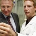 Minister Jäger und ein Wissenschaftler im Labor schauen sich Fingerabdrücke an. Sie stehen Bene einander. Minister Jäger links, in einem dunkelgrauen Anzug und rechts der Wissenschaftler in einem weißen Kittel.