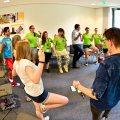 Staatssekretärin Milz steht mit Jugendlichen in einem Raum in einem Kreis und machen Sportübungen.