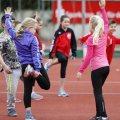 Mehrer Schulkinder machen Dehnübungen auf einem Tartan-Platz.