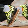 Füße in gelben Sportschuhen sind auf einem Startblock