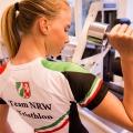 """Eine blonde Frau, ihr Haar zum Pferdeschwanz gebunden, stemmt mit der rechten Hand eine Hantel. Sie trägt ein weißes Trikot mit roten, grünen und schwarzen Elementen. Auf ihrem Rücken befindet sich das NRW-Wappen, darunter steht """"Team NRW Triathlon""""."""