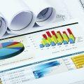 Verschiedene Statistiken und zusammengerollte Blätter liegen auf einem Tisch