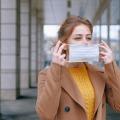Eine Frau setzt draußen eine Maske auf oder ab