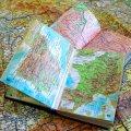 2 aufgeschlagene Landkartenbücher liegen auf einer großen Landkarte, die sich über das gesamte Bild erstreckt.