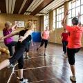 Neun Damen in Sportbekleidung stehen in der Mitte einer Sporthallte im Kreis und machen Aufwärmübungen.