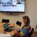 Eine Frau sitzt vor einem Laptop, an der Wand ist ein Bildschirm, auf welchem die Konferenz übertragen wird.
