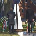 Zwei Männer stehen vor einem Gedenkstein, der mit zwei Blumenkränzen geschmückt ist