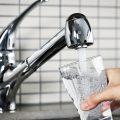 Ein Person füllt ein Glas mit Wasser aus dem Wasserhahn