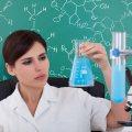 Eine dunkelhaarige Frau im weißen Kittel hält einen Glaskolben mit hellblauer Flüssigkeit in der linken Hand und schaut es prüfend an. Im Hintergrund eine grüne Tafel mit chemischen Formeln in weißer Kreideschrift.