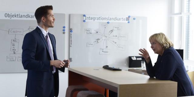 Ein Mitarbeiter erläutern der Ministerpräsidentin wie Softwareentwicklung funktioniert.