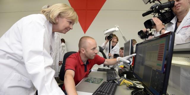 Ein Mitarbeiter zeigt Ministerpräsidentin Kraft etwas auf einem großen PC-Monitor