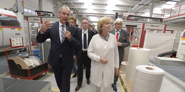 Ministerpräsidentin Kraft läuft durch die Produktionshalle