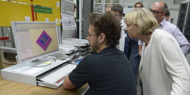 Ministerpräsidentin Kraft betrachtet ein 3D-Modell auf einem Monitor