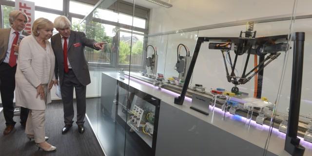 Ministerpräsidentin Kraft betrachtet eine Maschine mit Greifarmen