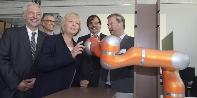 Ministerpräsidentin Kraft betrachtet einen orangenen Roboterarm
