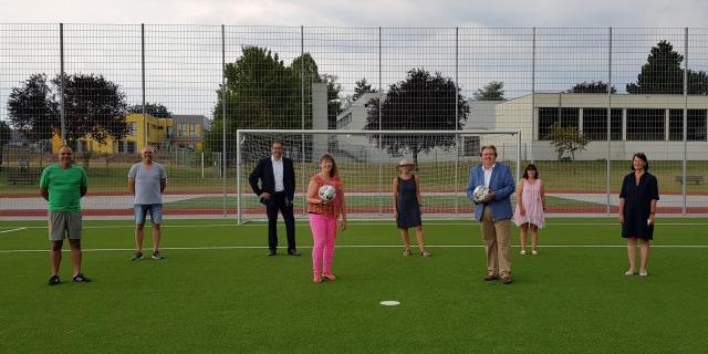 Staatssekretärin MIlz mit Vereinsmitgliedern vor dem Tor eines Rasen-Fußballplatzes. Sie in rosapinker Sportbekleidung mit einem Fußball in der Hand.