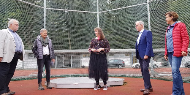 Staatssekretärin MIlz steht mit 4 Vereunsnutgkuedern an einer Hammerwurf-Sportstätte, hinter ihnne befindet sich ein Auffang-Stahlnetz.