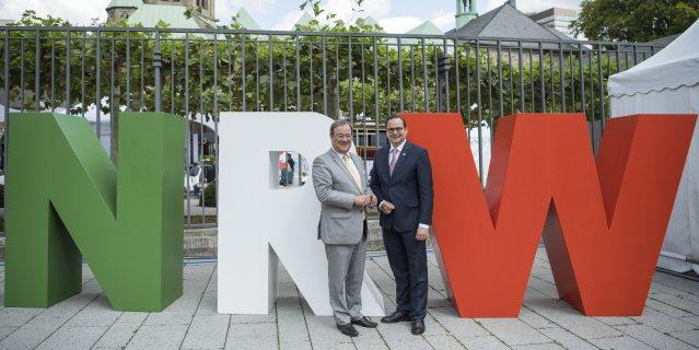 Herr Laschet und Herr Kufen stehen vor großen NRW-Buchstaben