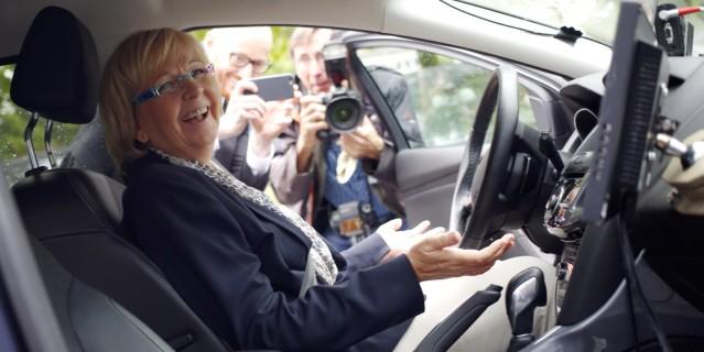 Ministerpräsidentin Kraft sitzt in einem offenen Auto und schau tin die Kamera