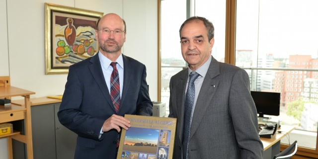 Das Foto zeigt Staatssekretär Lersch-Mense (links) der vom algerischen Generalkonsul Brahim (rechts) einen Bildband über Algerien überreicht bekommt.