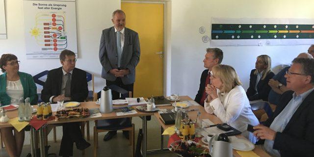 Bürgermeister Wilfried Roos steht und redet in einem Raum, seitlich sitzen Zuhörer