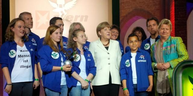 Das Foto zeigt Schülerinnen und Schüler der Gesamtschule Barmen bei der Preisverleihung mit Bundeskanzlerin Dr. Angela Merkel und Schulministerin Sylvia Löhrmann.