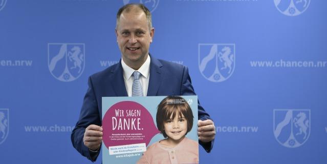 Ein Mann im Anzug steht vor einer blauen Wand und hält ein helblaues Plakat hoch, auf dem ein Kind zu sehen ist