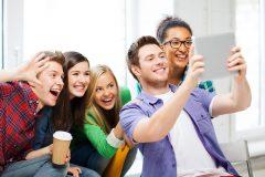 Das Foto zeigt mehrere lachende Jugendliche, die ein Selfie aufnehmen.