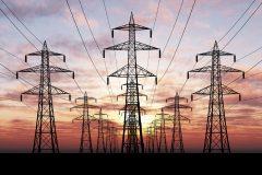 Das Bild zeigt mehrere Strommasten in der Dämmerung