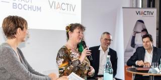 Staatssekretärin Andrea Milz mit einem Mikrofon in der Hand sitzt mit Teilnehmern der Pressekonferenz auf Hockern an Rundtischen. Hinter ihnen eine weiße Rückwand mit einer Präsentation.