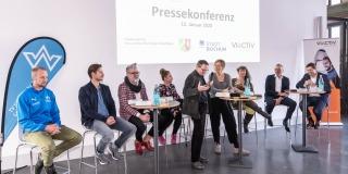 Staatssekretärin Andrea Milz sitzt mit Teilnehmern der Pressekonferenz auf Hockern an Rundtischen. Hinter ihnen eine weiße Rückwand mit einer Präsentation.