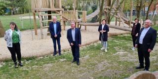Staatssekretärin Andrea Milz steht mit 5 weiteren Menschen auf einer Wiese vor einem Sandspielplatz mit vielen Holzgerüsten.
