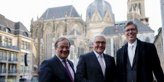 Ministerpräsident Laschet, Bundespräsident Steinmeier und eine weitere Person stehen vor dem Aachener Dom.