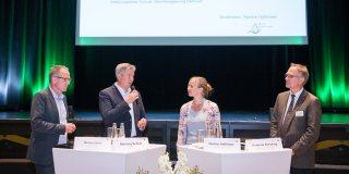 Ein Frau und drei Männer in einer Diskussionsrunde auf einer Bühne. Von links nach rechts: Herr Michael Uhlich, Herr Henning Schulz, Frau Nadine Haßlöwer und Herr Andreas Kersting.